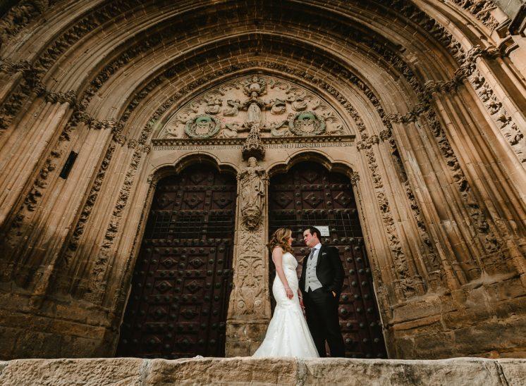Una pareja de novios vestidos como el día de su boda, en una puerta de una iglesia en la ciudad de Úbeda