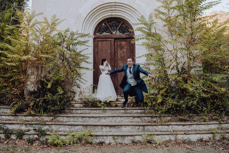 una pareja haciendo su trash the dress. se ve al novio saltando unas escaleras, mientras la novia se tapa la cara con las manos para no mirar.