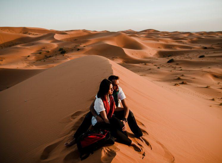 una pareja de jóvenes está sentada en lo alto de una duna del desierto observando la puesta de sol